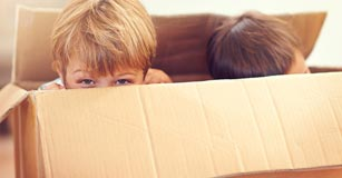Two kids playing in a box.